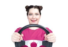 Happy young woman in pink t-shirt with steering wheel, isolated on white background. Front view. Female car driver concept royalty free stock images