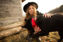 Happy young woman plaing with her black dog Brovko Vivchar in fron of old wooden house.  royalty free stock photos