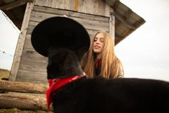 Happy young woman plaing with her black dog in fron of old wooden house. Girl tries a hat to her dog.  royalty free stock photography