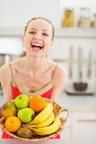 Happy young woman with plate of fruits Stock Photography