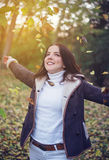 Happy young woman playing with autumn leaves Stock Photos