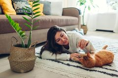 Young woman playing with cat on carpet at home. Master lying on floor with her pet stock images