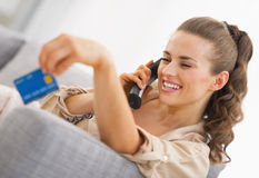 Happy young woman playing with credit card while talking phone Stock Image