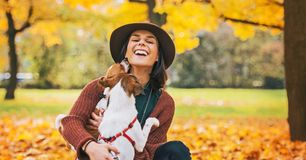 Happy young woman playing with dog outdoors in autumn Stock Images