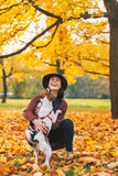 Happy young woman playing with dog outdoors in autumn Stock Photo