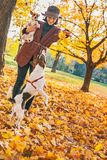 Happy young woman playing with dogs outdoors in autumn Royalty Free Stock Images