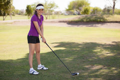 Happy young woman playing golf Stock Images