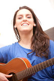 Happy young woman playing her guitar royalty free stock photos