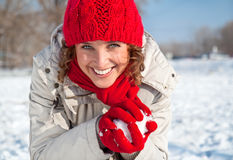 Happy young woman playing snowball fight. On the snow sunny day Royalty Free Stock Photos
