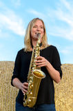 Happy young woman playing a tenor saxophone Royalty Free Stock Images