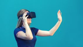 Happy young woman playing on VR glasses indoor. Virtual reality concept with young girl having fun with headset goggles. Touching air during VR experience royalty free stock photography