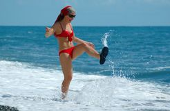 Happy young woman plays with water. On beach Royalty Free Stock Images
