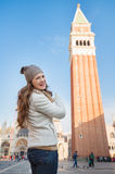 Happy young woman pointing on bell tower of St Marks Basilica Royalty Free Stock Photo