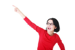 Happy young woman pointing on copy space Royalty Free Stock Photography