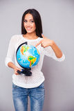 Happy young woman pointing finger at globe Stock Photos