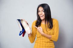 Happy young woman pointing finger on shoes Stock Photos