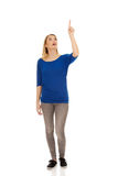 Happy young woman pointing up Royalty Free Stock Images