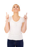 Happy young woman pointing up with both hands Royalty Free Stock Image