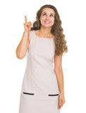 Happy young woman pointing up on copy space Royalty Free Stock Photo