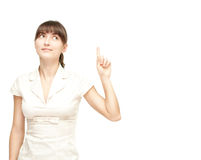 Happy young woman pointing upwards Stock Image