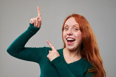 Happy young woman pointing upwards to a copy space royalty free stock image