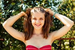 Happy young woman with ponytails at nature. Close-up portrait Royalty Free Stock Photography