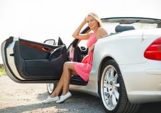 Happy young woman porisng in convertible car Royalty Free Stock Images