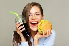 Happy young woman portrait with fast food. Burger and cola drink Stock Image