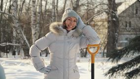 Happy young woman posing at camera with shovel in suburbs in winter. stock video