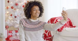 Happy young woman posing for a Christmas selfie Royalty Free Stock Image