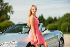 Happy young woman posing at convertible car Stock Photography