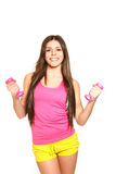 Happy young woman posing with a dumbbell on a white background Stock Image