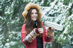 Happy young woman pouring hot drink from tourist matt vacuum flask to metallic cup in winter forest Stock Photography