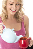 Happy Young Woman Pouring Tea from a Teapot Into Red Mug Stock Photography