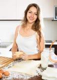 Happy young woman preparing dough Stock Photo
