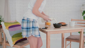 Happy young woman preparing flakes for breakfast and dancing in the light kitchen. Having fun in the morning. Royalty Free Stock Image