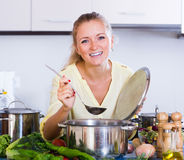 Happy young woman preparing  veggie soup. At home kitchen Stock Photo