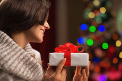 Happy young woman with present box in front of christmas lights Royalty Free Stock Images