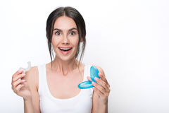 Happy young woman presenting clear aligners. Soon my teeth will be perfect. Portrait of joyful girl showing plastic prosthesis for clear-aligner treatment with royalty free stock photography