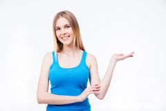 Happy young woman presenting something on the palm. Isolated on a white background. Looking at camera Stock Photography