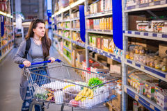Happy young woman pushing trolley in supermarket. Choose products royalty free stock images