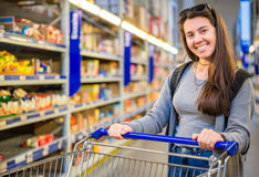 Happy young woman pushing trolley in supermarket. Choose products Stock Image
