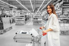 Happy young woman pushing trolley in supermarket. Black and white blur background stock photos