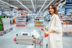 Happy young woman pushing trolley in supermarket. Blur background stock photo