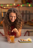 Happy young woman putting brown sugar cube into ginger tea Stock Photography