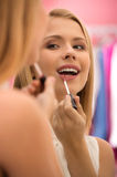 Happy young woman putting lipstick, Royalty Free Stock Photos