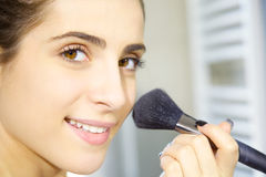 Happy young woman putting makeup in the morning in bathroom closeup Stock Photos