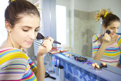 Happy young woman putting makeup in the morning in bathroom Stock Image