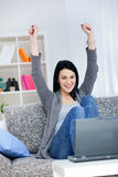 Happy young woman with raised hands. Happy young girl with raised arms sitting in bright living room and smiling, she has a laptop front her Stock Photos