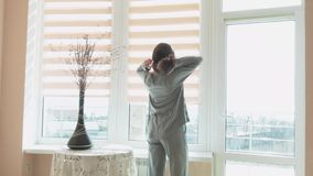 Happy young woman raises the curtain in the morning. Relax in the hotel by the sea. Vacation home stock video